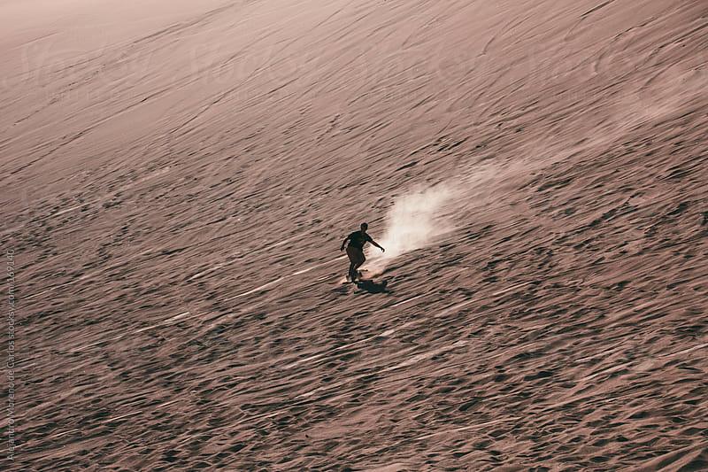Silhouette of man doing sandboard on desert dunes by Alejandro Moreno de Carlos for Stocksy United