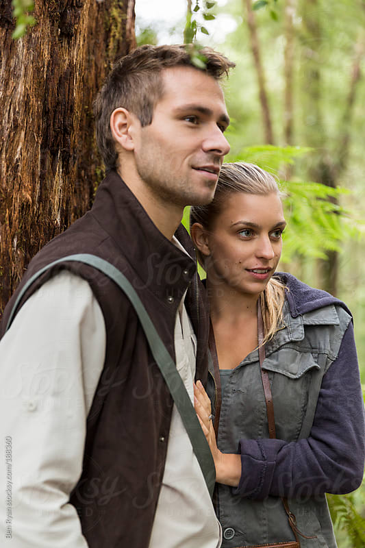 Young couple leaning against a tree whilst bushwalking by Ben Ryan for Stocksy United