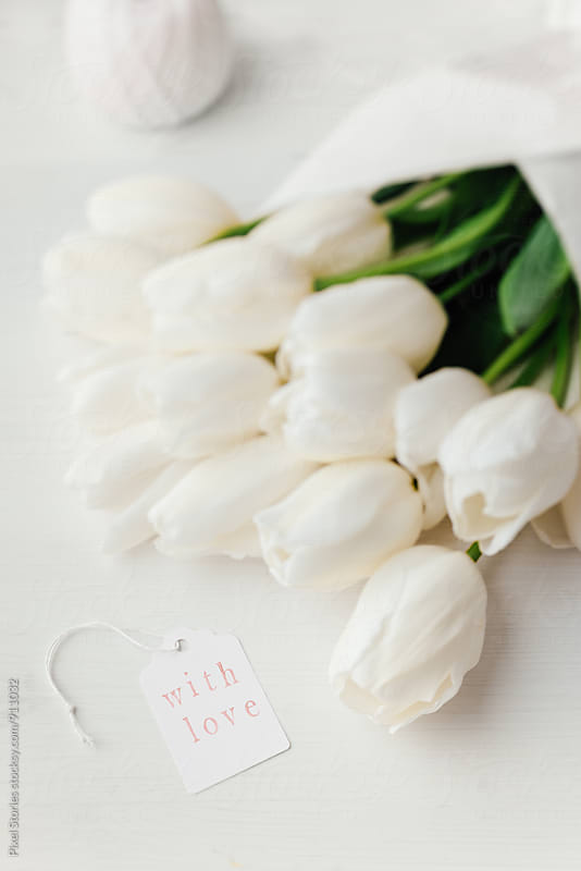 White tulips bouquet with tag by Pixel Stories for Stocksy United