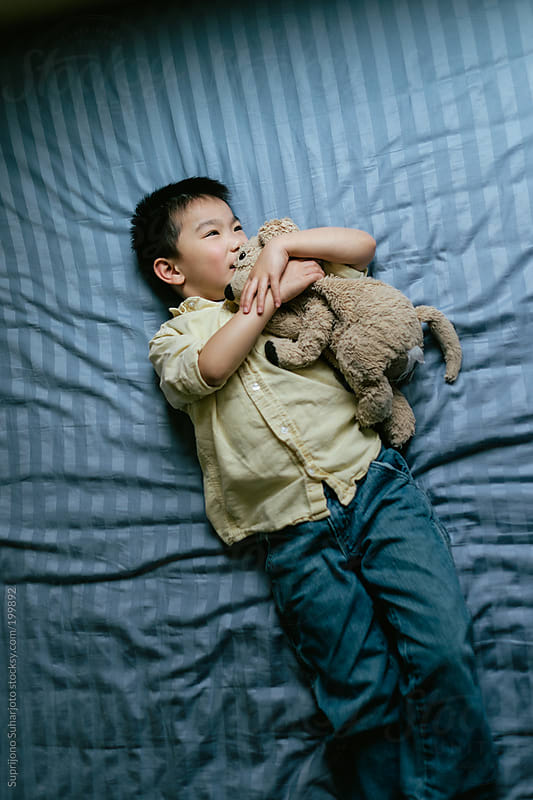 Asian kid playing with his stuffed animal on his bed  by Suprijono Suharjoto for Stocksy United