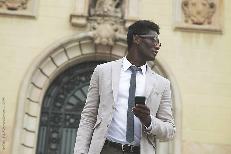 African young businessman with smartphone outdoors by BONNINSTUDIO for Stocksy United