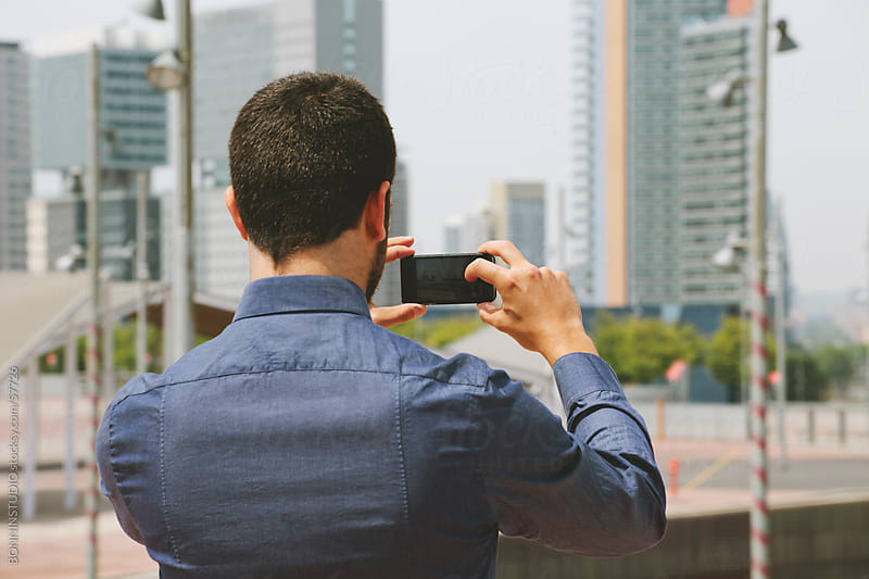 Young businessman taking pictures with mobile phone in a business district. by BONNINSTUDIO for Stocksy United