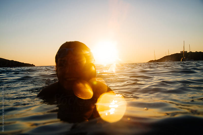 Young woman enjoying the sunset in water by Boris Jovanovic for Stocksy United