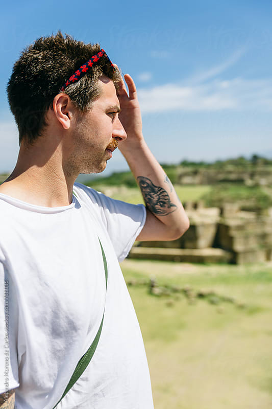 Young man tourist with a tiger tattoo on his arm looking at ancient ruins landmark in Mexico by Alejandro Moreno de Carlos for Stocksy United