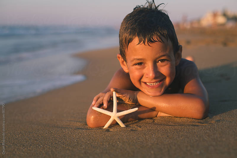 Child looking in to a starfish by Dejan Ristovski for Stocksy United