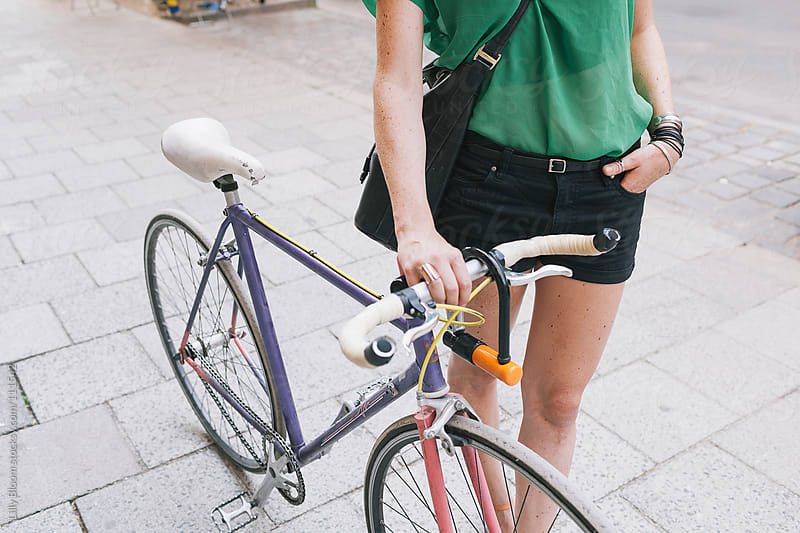 Young woman with a fixed gear bike in an urban environment by Lilly Bloom for Stocksy United