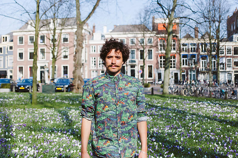 Young stylish man standing in a grass field with flowers with a flower shirt on. by Denni Van Huis for Stocksy United