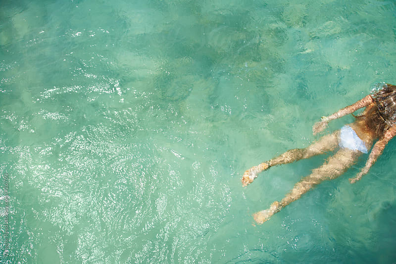 Beautiful woman floating in the ocean by Trinette Reed for Stocksy United