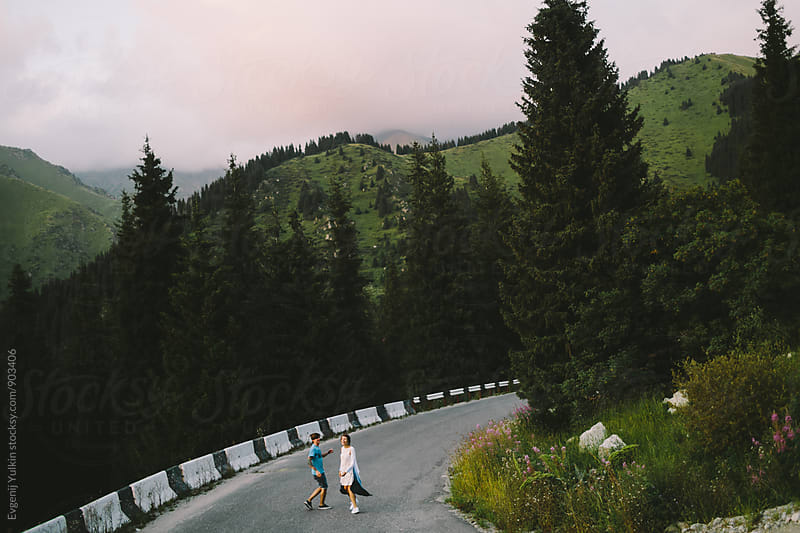 Young couple on the mountain road by Evgenij Yulkin for Stocksy United