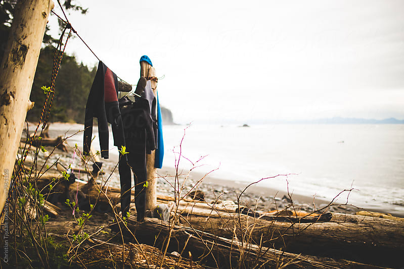 Wetsuits hanging on a clothesline on a beach in the PNW by Christian Tisdale for Stocksy United