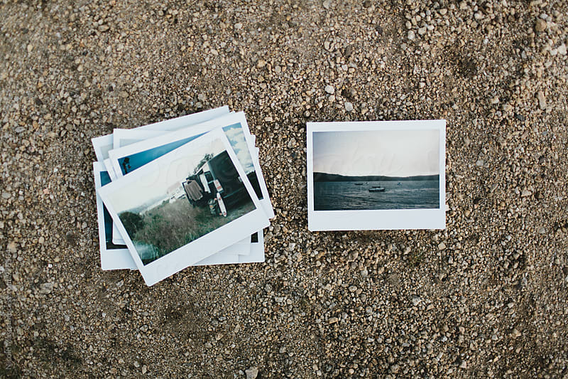 stack of instant photos next to one photograph on ground by Nicole Mason for Stocksy United