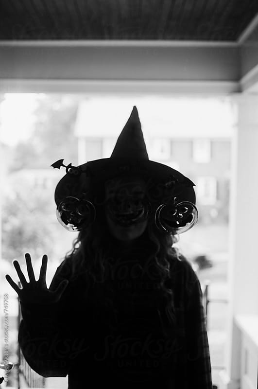 A woman dressed as a witch at the front door by Chelsea Victoria for Stocksy United