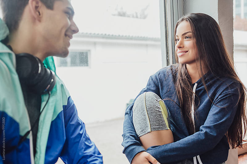 Man and Woman in Sportswear Sitting and Chatting in the Gym by Lumina for Stocksy United