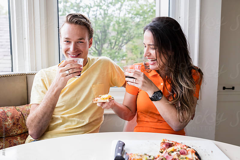 Couple Eating Pizza in Kitchen by Jill Chen for Stocksy United
