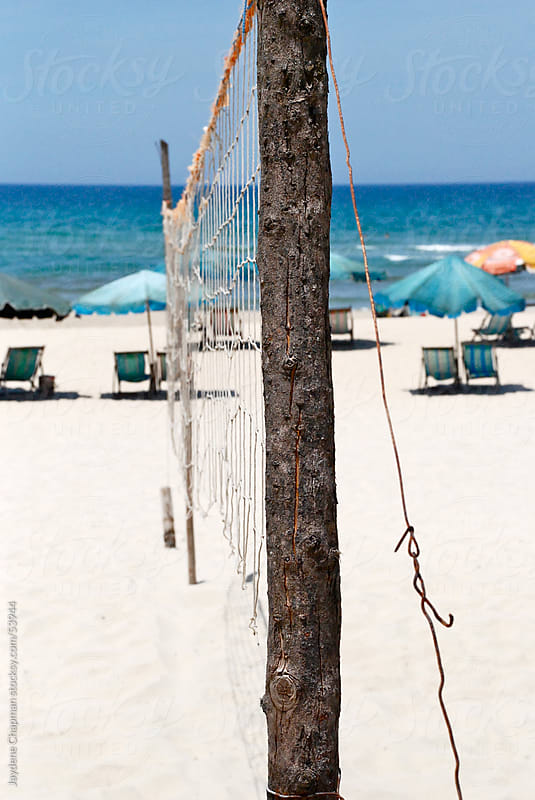 Handmade beach volleyball net overlooking umbrellas and deck chairs sea side, China Beach, Vietnam by Jaydene Chapman for Stocksy United