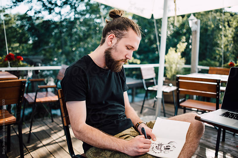 Man drawing an illustration in the sketchbook by Boris Jovanovic for Stocksy United