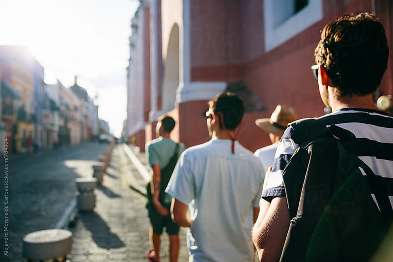 Back view of a group of  young men walking on the path of a colorful street by Alejandro Moreno de Carlos for Stocksy United