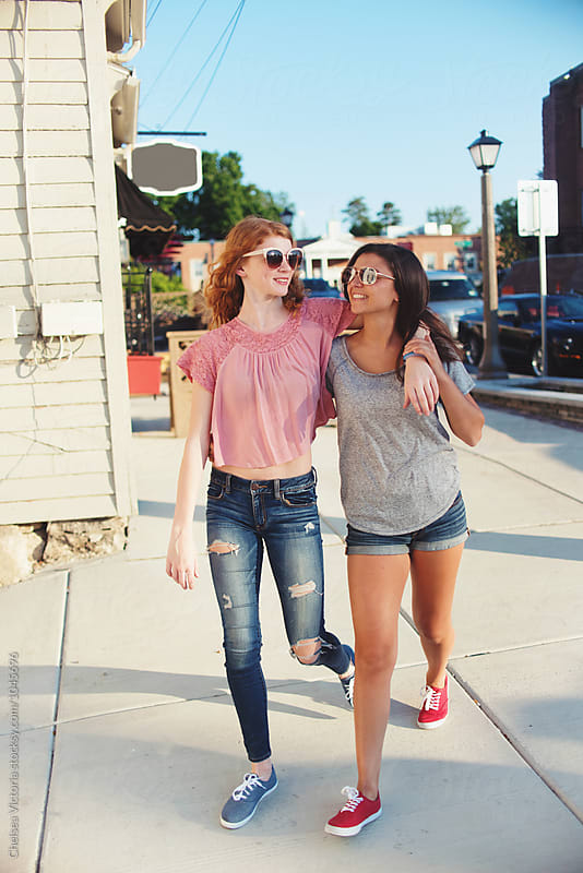Two friends walking down the street in the summertime by Chelsea Victoria for Stocksy United