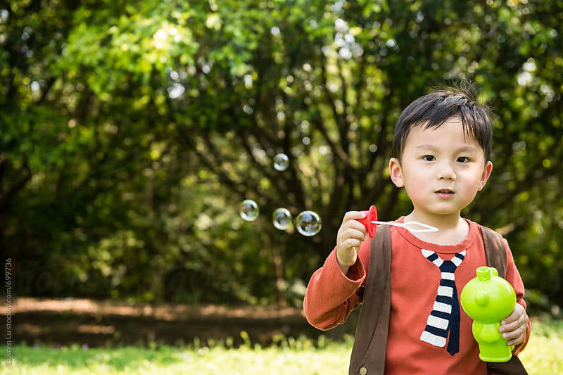Kid blowing bubbles at park by Lawren Lu for Stocksy United