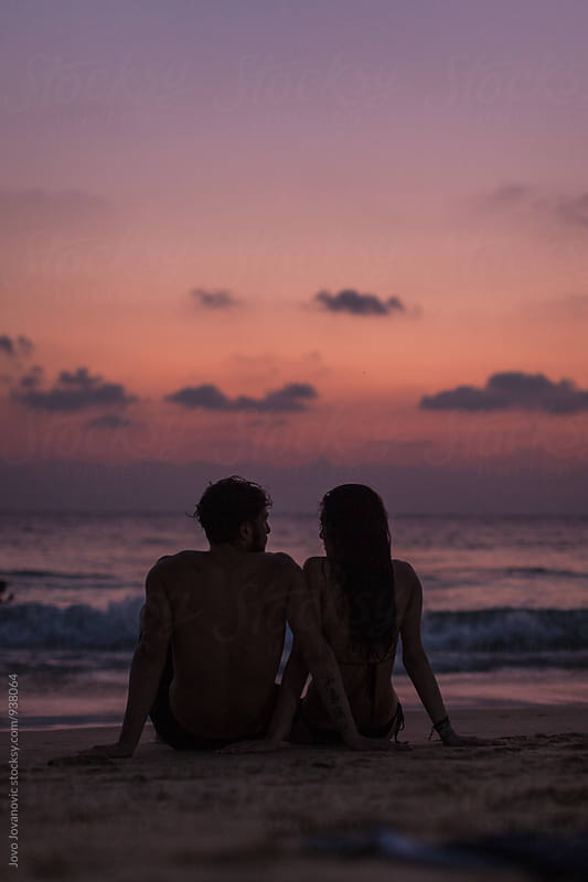 Romantic couple on the beach at colorful sunset in background by Jovo Jovanovic for Stocksy United