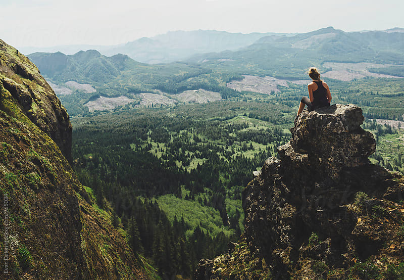 Woman Sitting on Mountain Cliff by Evan Dalen for Stocksy United