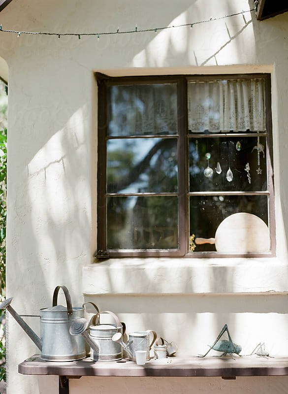 An outdoor scene of watering cans on a shelf outside a California home. by Kelsey Gerhard for Stocksy United