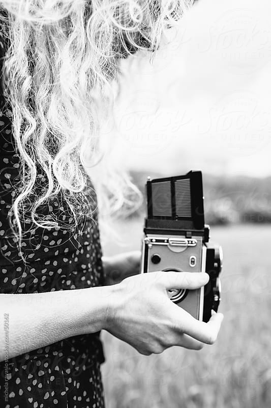 Woman taking a photo with vintage camera by michela ravasio for Stocksy United