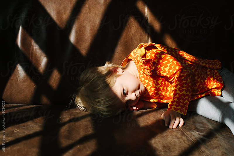 Little girl lies in intense light and shadow on brown couch. by Julia Forsman for Stocksy United