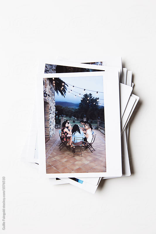 Polaroid shots in stack on white table by Guille Faingold for Stocksy United