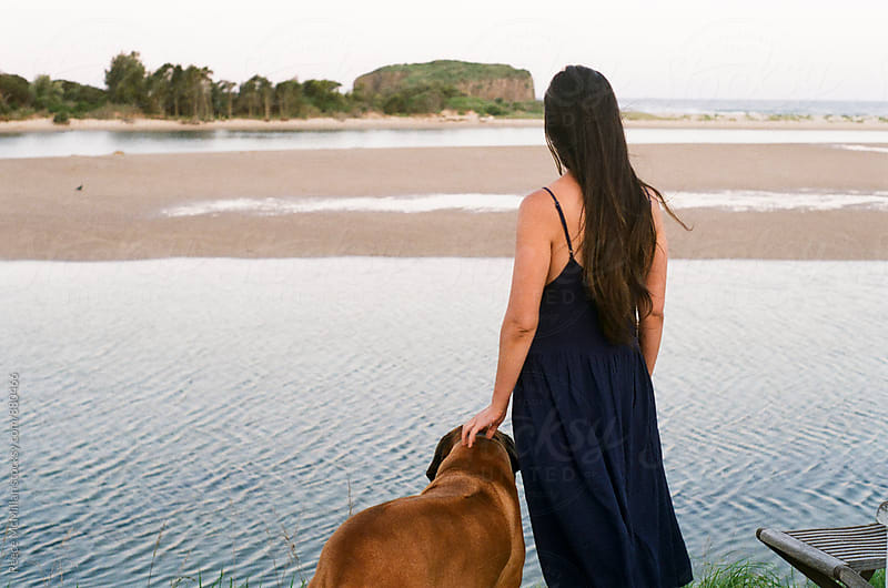 Woman with dog at the coast by Reece McMillan for Stocksy United
