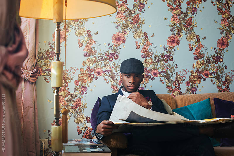 Elegant Young Black Man Reading Newspaper in Ornate Stylish Living Room by Julien L. Balmer for Stocksy United