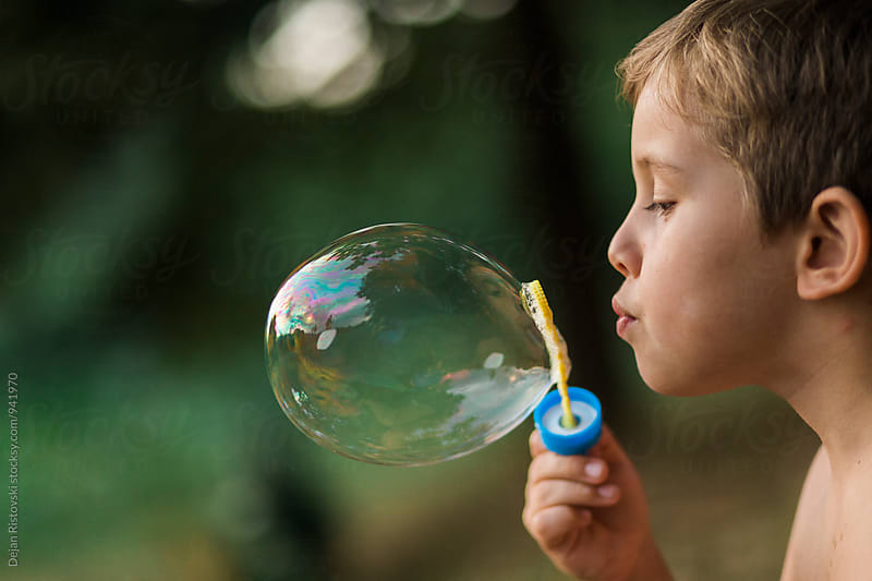 Boy blowing soap bubble. by Dejan Ristovski for Stocksy United
