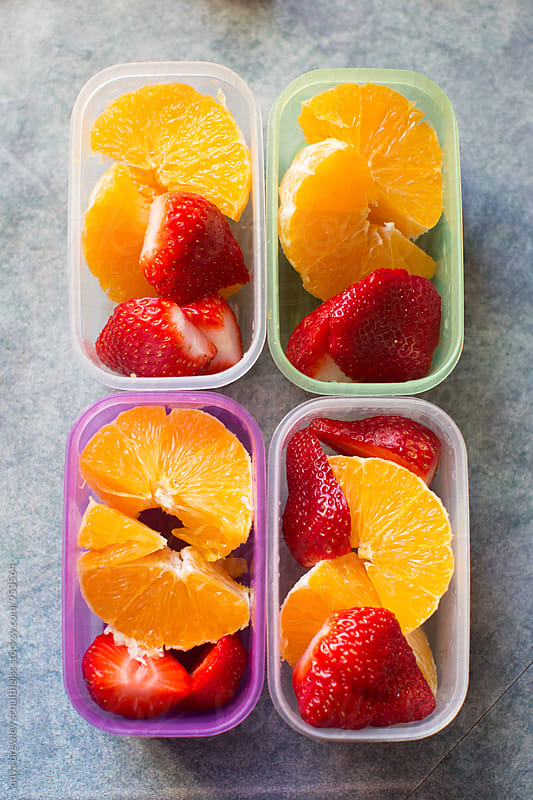 Containers of peeled and cut oranges and strawberries by anya brewley schultheiss for Stocksy United