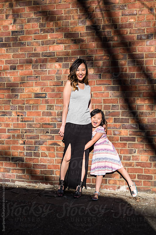 Happy Asian mother and daughter having fun together by Suprijono Suharjoto for Stocksy United