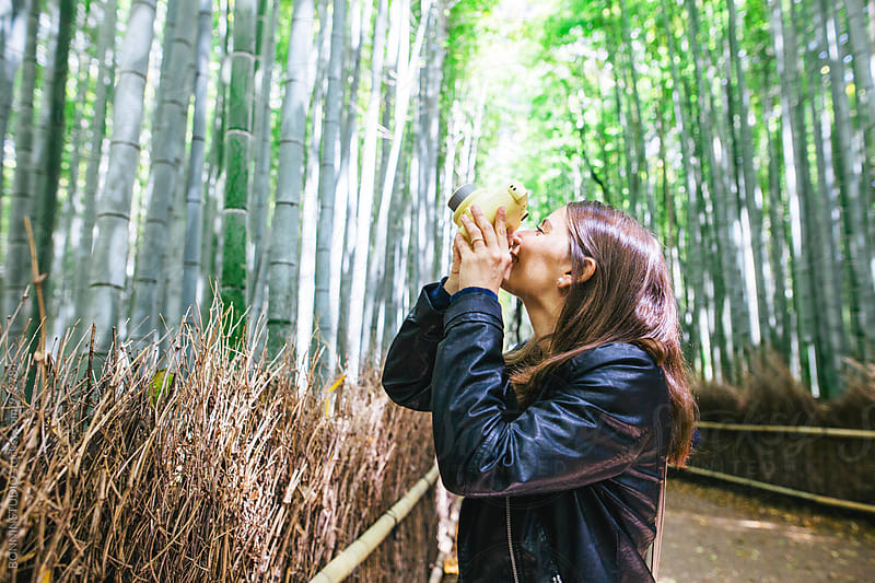 Side view of a tourist taking a photo of bamboo forest. by BONNINSTUDIO for Stocksy United