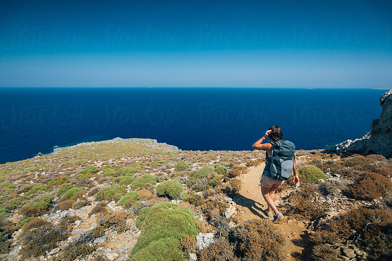 Female hiker walking a trail overlooking the sea by Micky Wiswedel for Stocksy United
