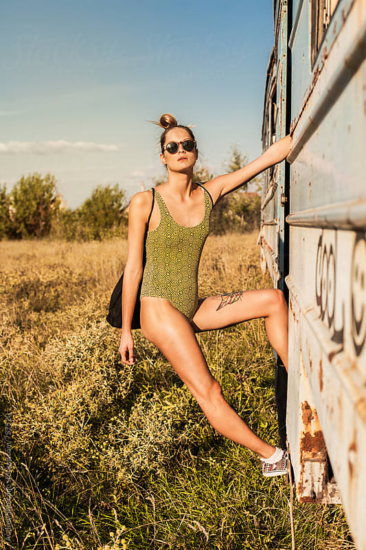 HIp young woman on tricot  hanigng from rusty train with field and sky in backgorund. by Marko Milanovic for Stocksy United
