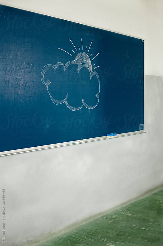 Old  blue blackboard with cloud and sun drawing by Miquel Llonch for Stocksy United