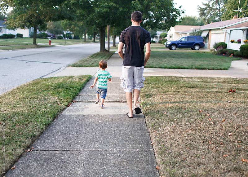 father and son walk down sidewalk by Maria Manco for Stocksy United