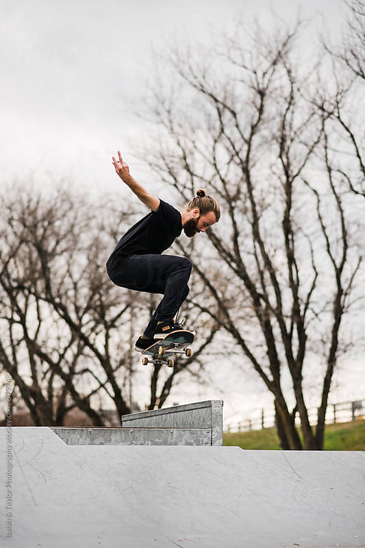 Man doing ollie in air by Isaiah & Taylor Photography for Stocksy United