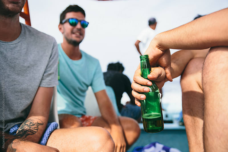 Front view of man's hand holding a green beer bottle outdoors on a sunny day with friends by Alejandro Moreno de Carlos for Stocksy United