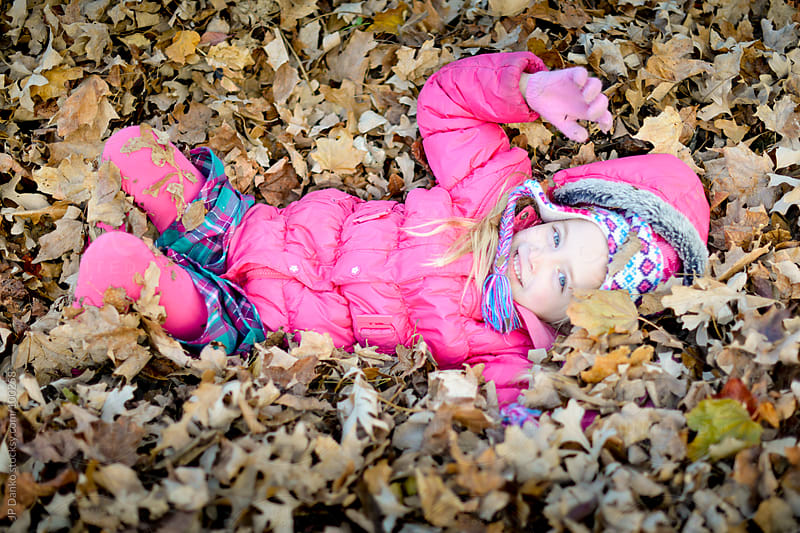 Little Girl Laying In Fall Leaf Pile in Autumn by JP Danko for Stocksy United