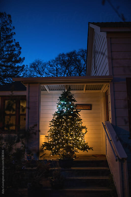 Christmas tree on porch by Amy Covington for Stocksy United
