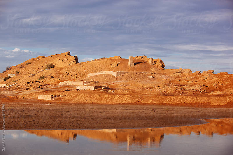 Golden desert mountain with some ruins reflecting in an ocean pool by Gary Parker for Stocksy United