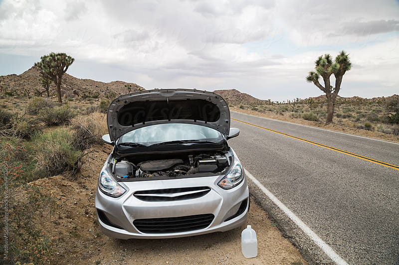 Car broken down on side of road in desert by Matthew Spaulding for Stocksy United