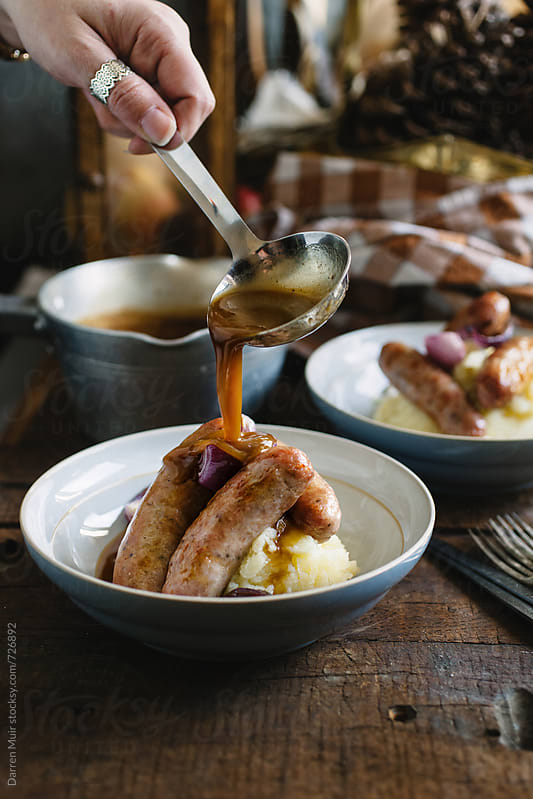 Woman's hand pouring gravy over a bowl of bangers and mash. by Darren Muir for Stocksy United