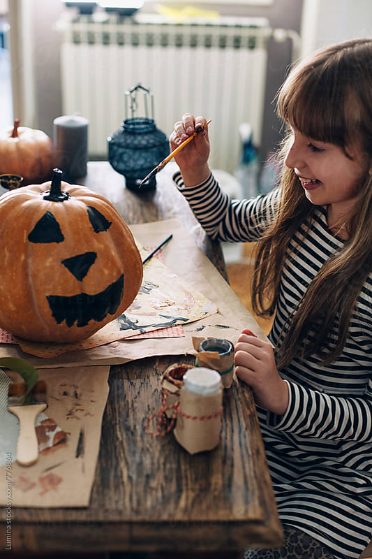 Happy Girl Decorating a Pumpkin for Halloween by Lumina for Stocksy United