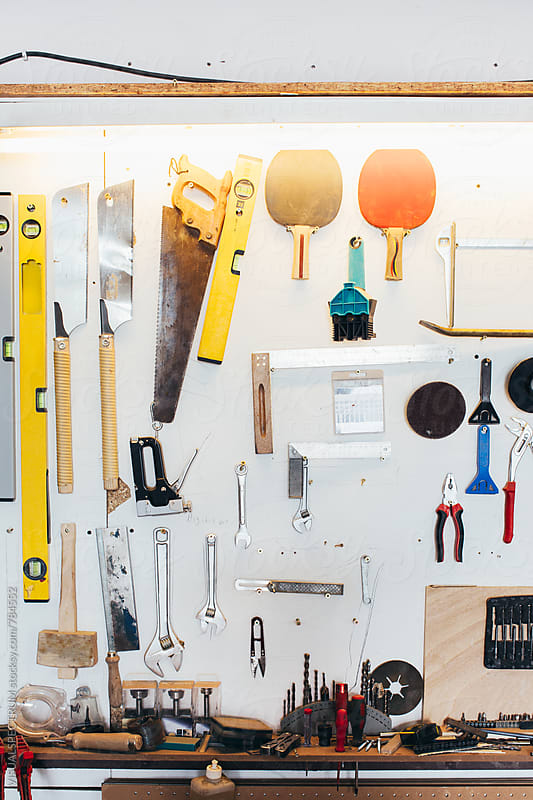Carpenter Tools Hanging on White Wall by VISUALSPECTRUM for Stocksy United