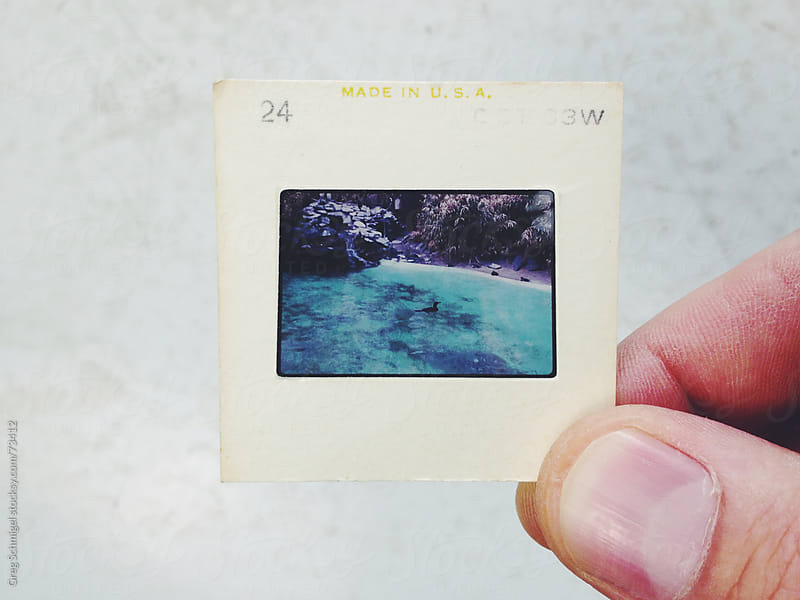 Vintage 35mm film slides on an old white table by Greg Schmigel for Stocksy United