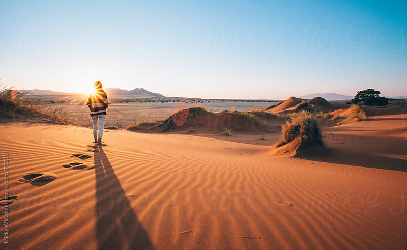Woman enjoying sunset on a desert dune by Micky Wiswedel for Stocksy United